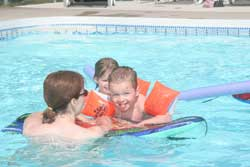 naturist mother and kids in the pool