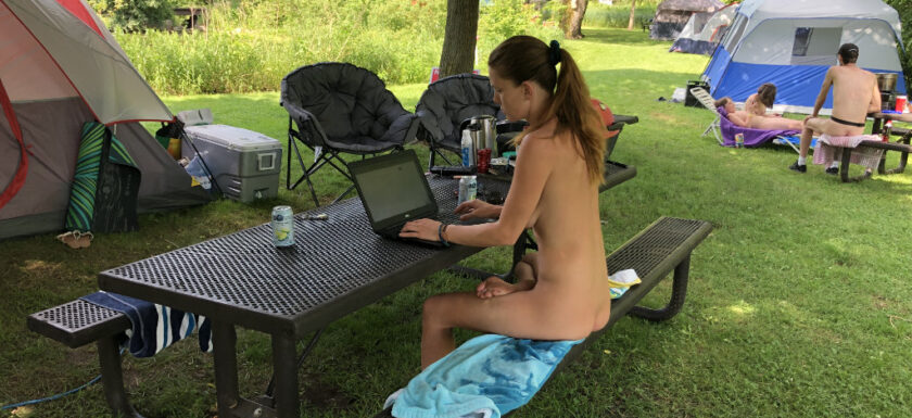 Working on a laptop outside at Bare Oaks Family Naturist Park